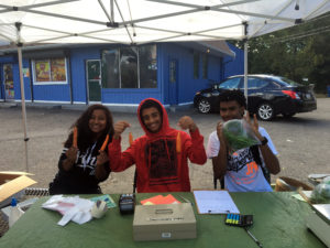 Three Common Ground students work at the Mobile Market in Scantlebury Park.